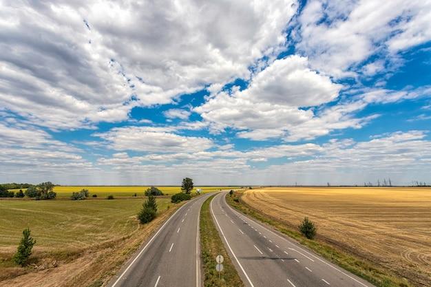 Snelweg door de velden tegen een blauwe hemel met mooie witte wolken