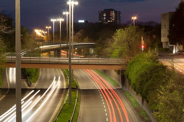 Snelweg met stedelijk nachtverkeer met focus op de weg