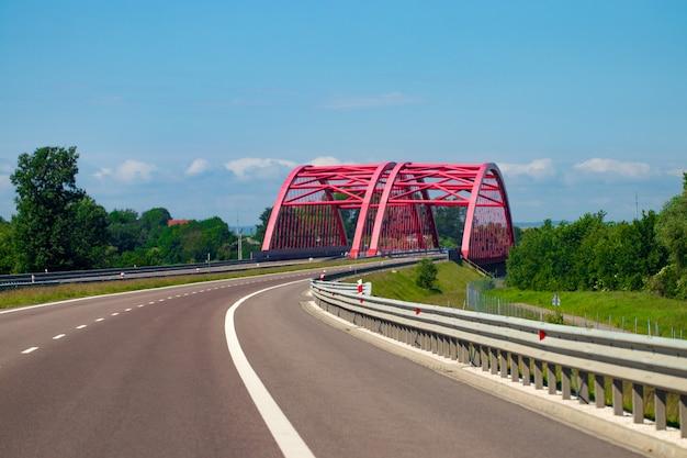 Snelweg uitwisseling met brug en zon op de achtergrond.