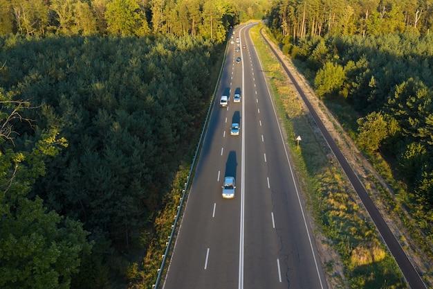 Snelweg weg met passerende auto's in het bos bij zonsondergang.