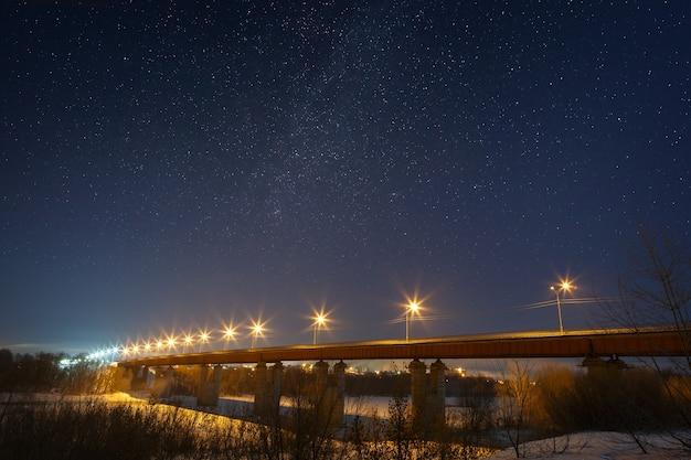 Snelwegbrug met de sterren en de melkweg, verlicht door lantaarns