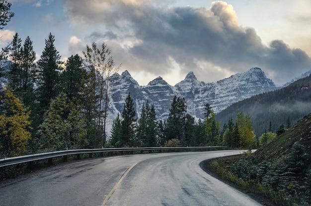 Snelwegweg met rotsachtige bergen in dennenbos bij morenemeer in het nationale park van banff