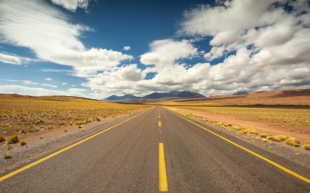 Snelwegweg, zand en vulkaan in de atacama-woestijn in chili, zuid-amerika