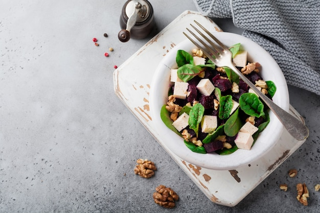 Snijbiet, rucola, rode biet, ricotta en walnotensalade met olijfolie in een keramische oude plaat op een grijze steen of betonnen verouderd oppervlak. selectieve aandacht. bovenaanzicht.