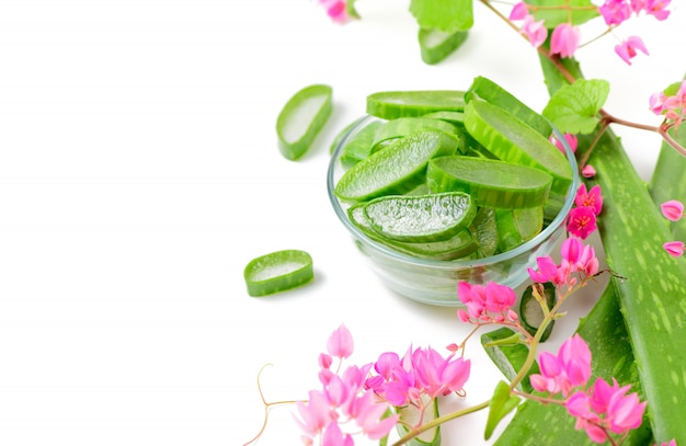 Snijd aloë vera in glas met roze die klimplant op wit wordt geïsoleerd.