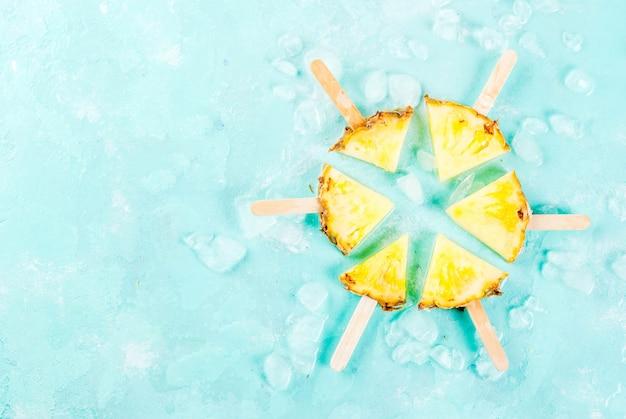 Snijd ananas ijslollystokjes en muntblaadjes