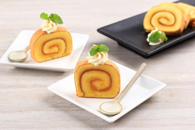Snijd ananasbroodjescake of bolu gulung nanas, dunne cake gerold met ananasjam met kaasglazuur erop.