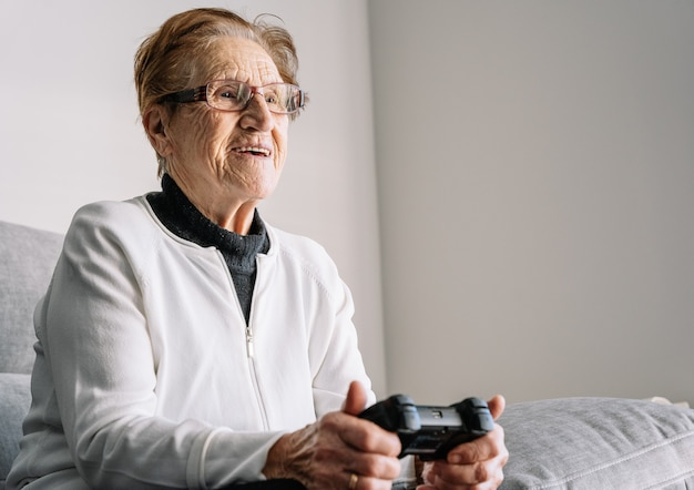 Snijd anonieme 90-jarige vrouw zittend op de bank met moderne controller en thuis videogames spelen