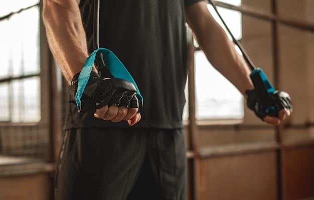 Snijd anonieme gespierde mannelijke atleet doen oefening met elastische touwen tijdens intense functionele training in de sportschool