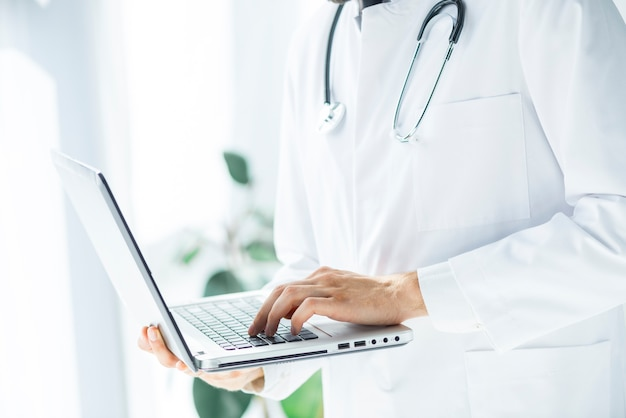 Snijd arts doorbladerend laptop in bureau