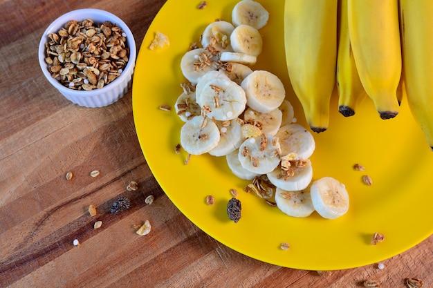 Snijd banaan met muesli op een gele plaat op een rustieke houten, bovenaanzicht