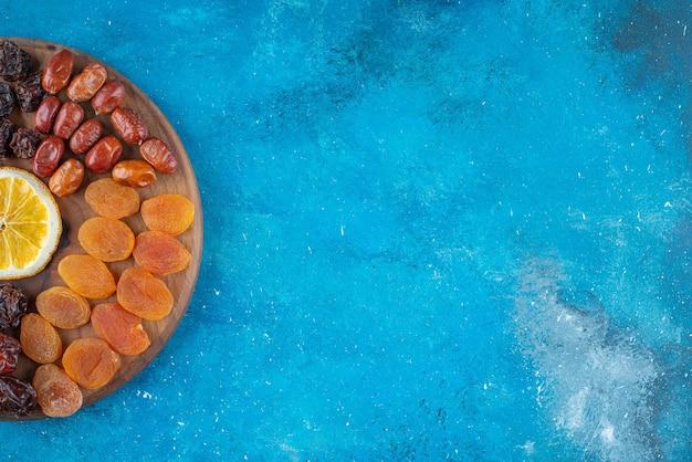 Snijd citroen en gedroogd fruit op een bord op het blauwe oppervlak