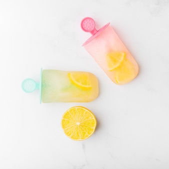 Snijd citroen en verse ijslolly met citrus op kleurrijke stokken