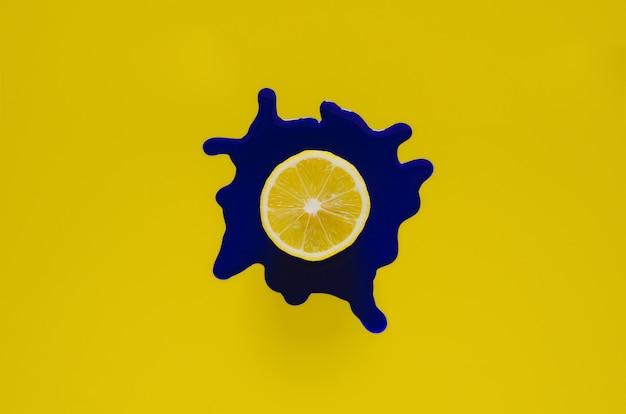 Snijd citroen op donkerblauwe posterkleur die op gele achtergrond laat vallen