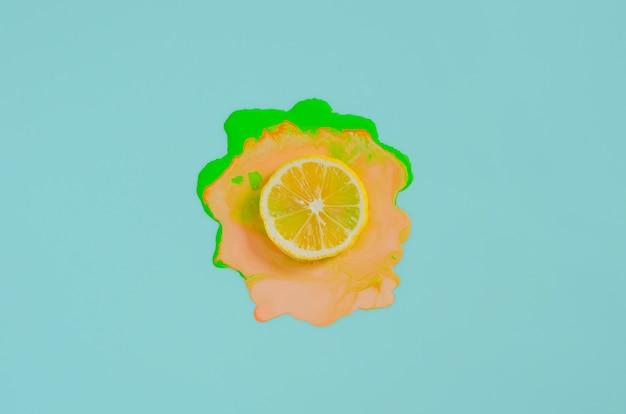 Snijd citroen op kleurrijke posterkleur die op blauwe achtergrond laat vallen. minimaal zomerconcept.