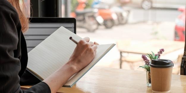 Snijd close-up van een vrouw die online op afstand studeert op een laptop, maak een notitie in een notitieboekje dat thuis op een bureau zit. slimme vrouwelijke schrijver of student handschrift in briefpapier kladblok, planning of lijst maken.