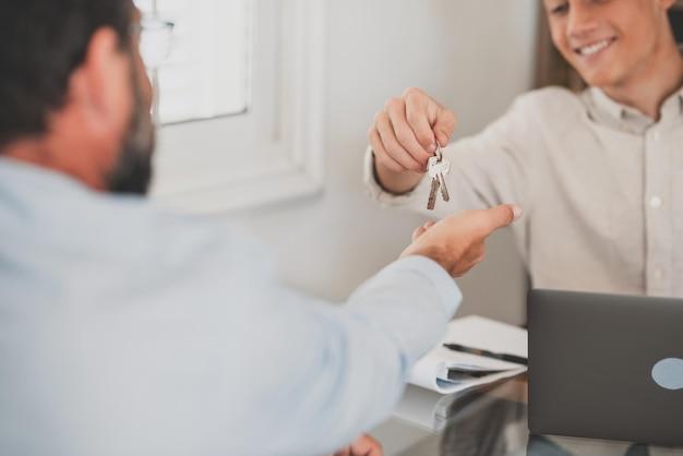 Snijd close-up van makelaar en geef sleutels aan mankoper of huurder die het eerste huis van een agentschap koopt. makelaar of makelaar feliciteren mannelijke huurder met de aankoop van een huis of appartement. eigendom, huurconcept.