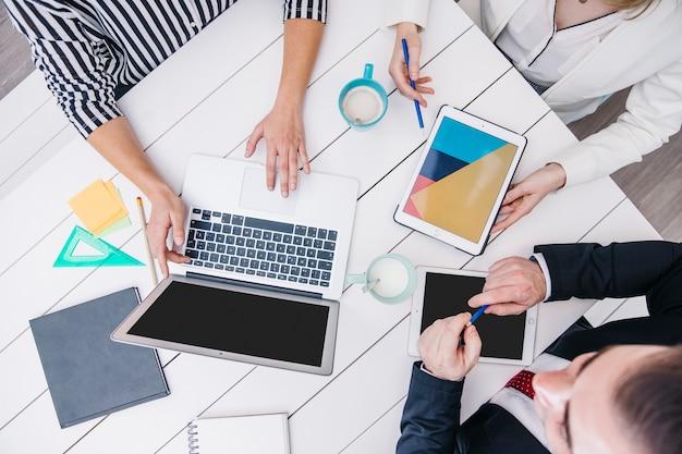 Snijd collega's met behulp van moderne apparaten aan een bureau