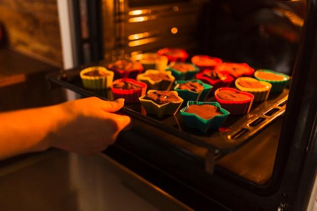 Snijd de hand die cupcakes in de oven legt