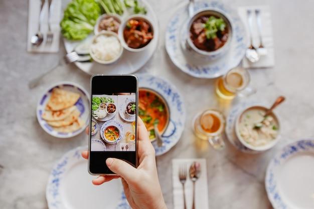 Snijd de hand in die foto's van voedsel op tafel neemt