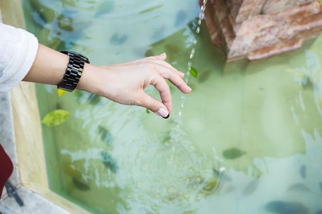 Snijd de hand in met het gooien van munten in de fontein
