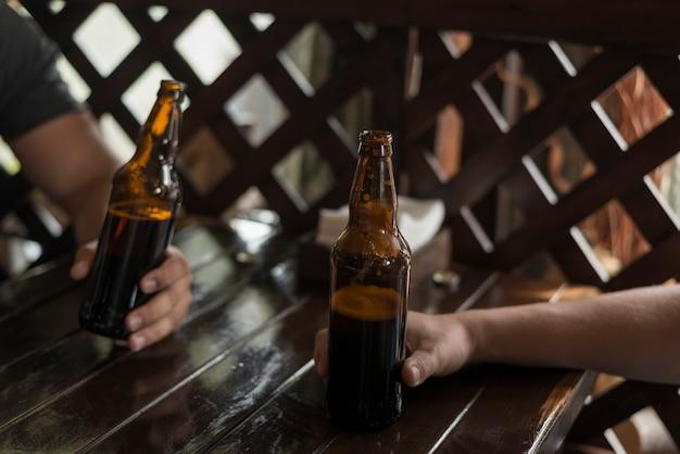 Snijd de handen bij met bier op tafel