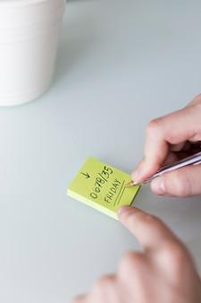 Snijd de handen bij terwijl u informatie op een notitie achterlaat