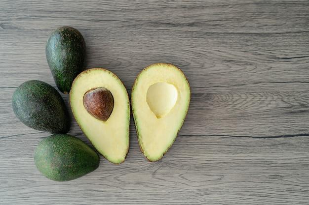 Snijd de helft, gesneden verse groene avocado op bruine houten tafel. vruchten gezond voedsel concept.