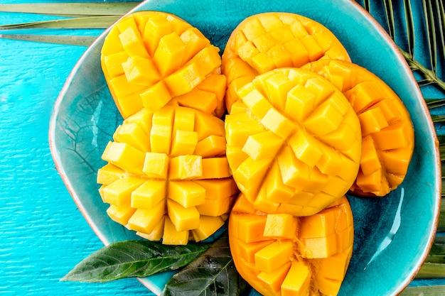 Snijd de mango op een blauw bord