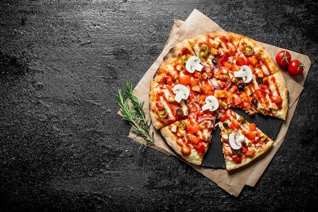 Snijd de mexicaanse pizza op het papier. op zwarte rustieke achtergrond