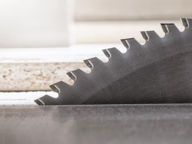 Snijd de onderdelen van spaanplaat op een cirkelzaag in een meubelfabriek.