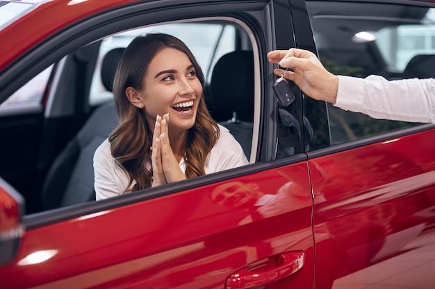 Snijd de showroomagent die de sleutel geeft aan de verbaasde vrouwelijke klant die in de auto zit en in de handen klapt