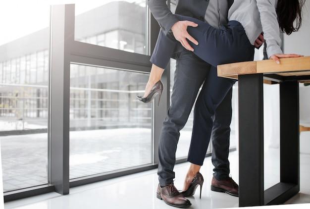 Snijd de weergave van de man in pakstand en houd het been van de vrouw in seksuele pose. ze zit op tafel.