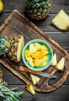 Snijd een ananas in een kom en op een snijplank met een mes. op houten