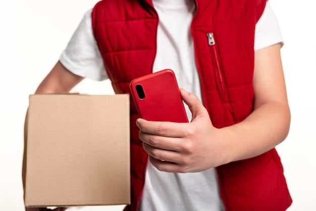 Snijd een anonieme bezorger bij in een rood uniform, scant kartonnen doos met mobiele telefoon tijdens het bezorgen van het pakket