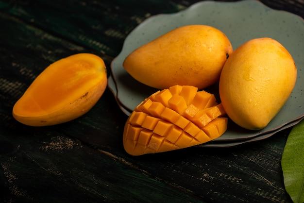 Snijd en voltooi mango's op een bord in een donkere omgeving