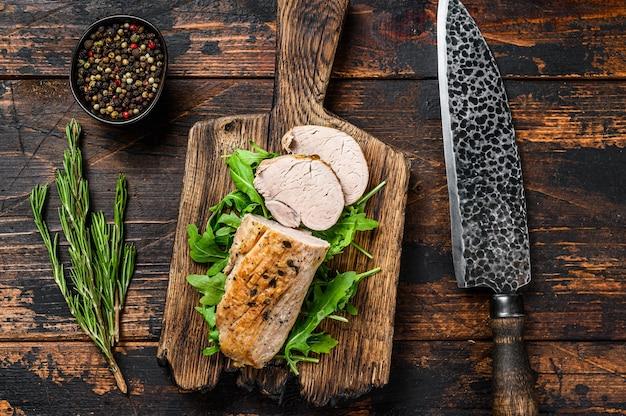 Snijd gebakken varkenshaas biefstuk op een snijplank met rucola. donkere achtergrond. bovenaanzicht.