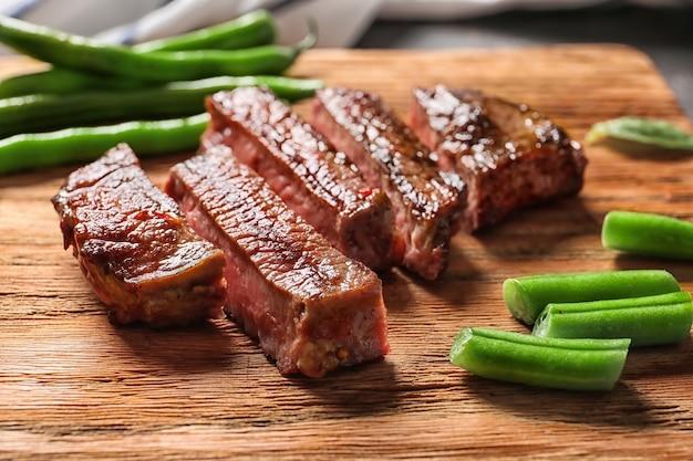 Snijd gegrilde steak met sperziebonen op houten plank