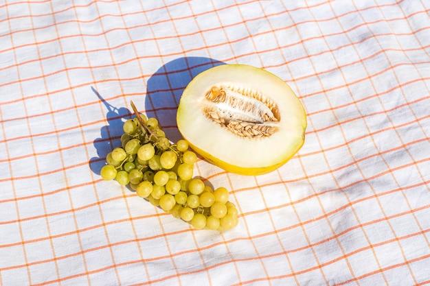 Snijd gele meloen, druiven op het tafelkleed. bovenaanzicht, plat gelegd.