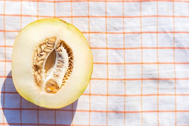 Snijd gele meloen op een tafelkleed. bovenaanzicht, plat gelegd.