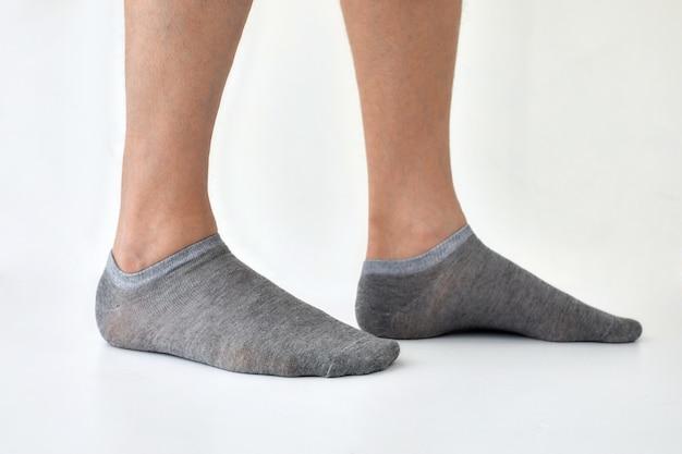 Snijd gezichtsloze man in grijze sokken die in lichte studio staan
