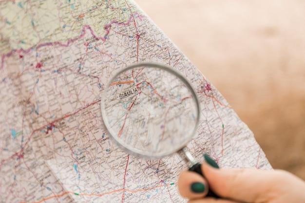 Snijd hand met vergrootglas die kaart onderzoeken