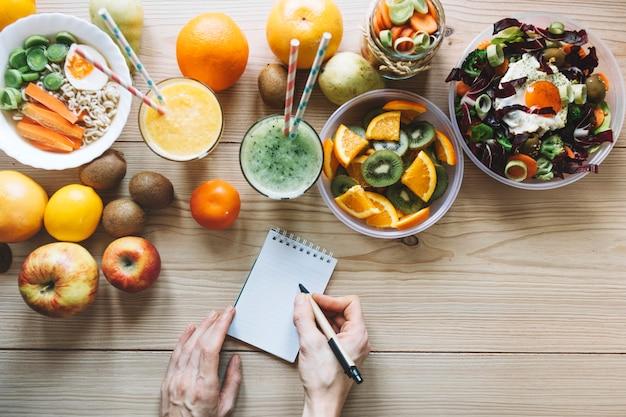 Snijd handen bij het maken van notities in de buurt van gezond voedsel