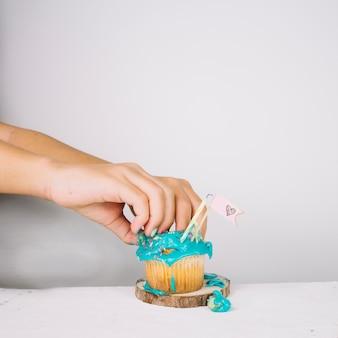 Snijd handen die cupcake verpletteren