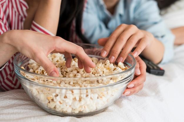 Snijd handen van vrouwen die popcorn eten