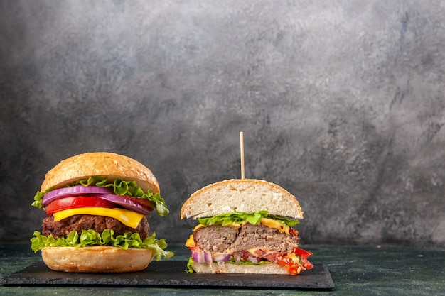 Snijd hele smakelijke sandwiches op een zwart dienblad op een donker gemengd kleuroppervlak