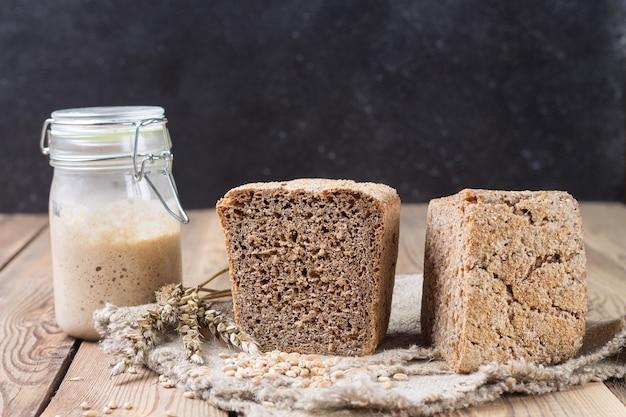 Snijd het brood half, van de bloem van het speltmeel in het voorgerecht zit op de randen van de mat op een natuurlijke houten achtergrond