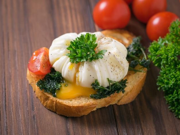 Snijd het gepocheerde ei op een stuk gebakken brood met kruiden. vegetarische snack met gepocheerde eieren.