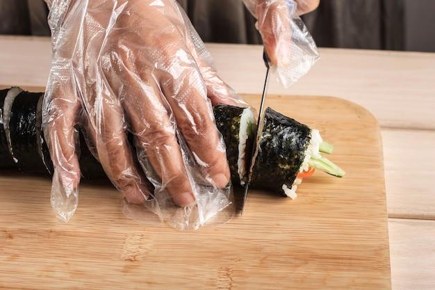 Snijd kimbap (koreaanse roll rice dish) met blauw mes. vrouwenhand die plastic handschoen dragen, gimbap maken, kimbap knippen, koreaanse roll gimbap (kimbob of kimbap). stap voor stap kimbop maken