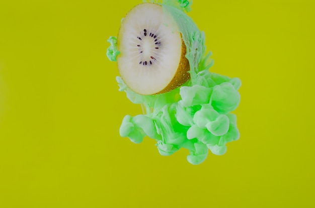 Snijd kiwi met gedeeltelijke focus van het oplossen van groene poster kleur in water